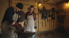 Blacksmith demonstrates process of forging iron standing next to a smiling woman Stock Footage