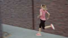Woman running, sprinting on the sidewalk - interval run Arkistovideo