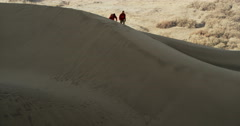Reveal of two hikers going over sand dune ridge in the desert slow motion Stock Footage