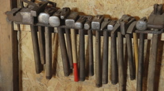 Different hammers hanging on wall for forging a metal closeup Stock Footage