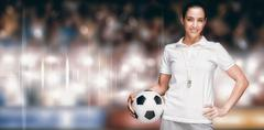 Female athlete holding a soccer ball against sports arena - stock photo