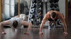 Tubby guy looks at the trainer, struggling to do push-ups, but falls due to Stock Footage