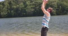 Jump to Catch Football on Beach at Lake a Young Man Slow Motion Stock Footage