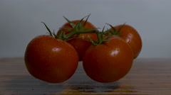 Four tomatoes are dropped onto a cutting board in slow motion and bounce Stock Footage