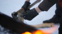 In winter, a man wearing gloves chopping wood with an ax on a background of fire Stock Footage
