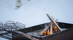 Close to grating lying on a brazier burning flames on a background of snow and Stock Footage