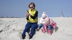 Mom with smart phone and kids playing on a sea shore sand Stock Footage