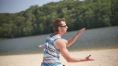 Running and Catching Frisbee Flying on Beach at Lake Slow Motion - stock footage