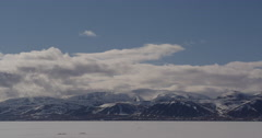 Time lapse - clouds race over snowy mountains across sea ice Stock Footage