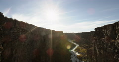 Sunset over river in a canyon tracking camera past climbing rope Stock Footage