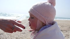 Mother gives child daughter drink clean pure water from glass on sea shore Stock Footage