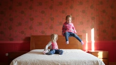 Two little cute child girls happily playing on a big parental bed slow motion - stock footage