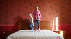 Two little cute child girls happily jumping playing on a big parental bed - stock footage