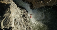 Two mountain climbers on ropes spinning over a waterfall in a deep cabin Stock Footage