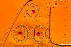 Old orange painted aircraft fuselage part. Stock Photos