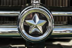 Chrome star on the radiator grille of an old car. - stock photo