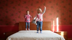 Two little cute child girls happily jumping on a big parental bed slow motion - stock footage