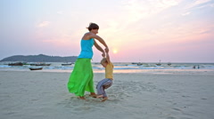 Mother swinging toddler son by hands on beach Stock Footage