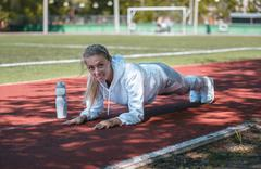 Squatting.young beauty girl do exercises at the stadium Stock Photos