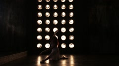 Dancing Female Silhouette. Girl on Pointe dancing on wall background with lamps Stock Footage