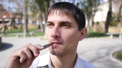 Portrait man smoking electronic cigarette breathing out smoke slow motion Stock Footage