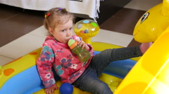 Little child girl playing drinking a beverage from a bottle nipple Stock Footage
