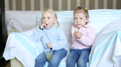 Cute little child girls on a chair watching cartoons and eating tasty snacks  Stock Footage