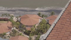 Clay Roof in Foreground of Waves Splashing on Tropical Beach Stock Footage