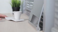 Girl drinks coffee from a white mug and beautiful prints on the tablet Stock Footage