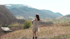Young beautiful female model in a landscape with mountains and village Stock Footage
