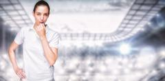 Female athlete blowing a whistle  against sports arena - stock photo