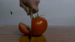 A single ripe tomato on a cutting board, a knife cuts it in slow motion, 2 Stock Footage