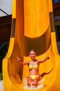 Child on water slide at aquapark shows thumbs up. Kuvituskuvat