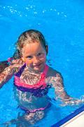 Child swim in blue water into swimming pool. Kuvituskuvat