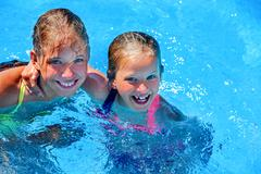 Two different ages children swim in swimming pool. Kuvituskuvat