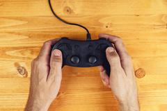 Hands using gamepad controller on wooden desk, top view - stock photo