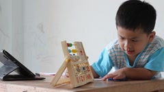 Little boy practise a brains by wooden toy on the table, Stock Footage