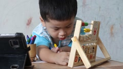 Boy playing toys on the wooden table Stock Footage