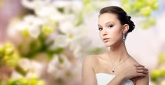 beautiful asian woman with earring and pendant - stock photo