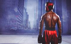 Rear view of boxer standing against urban projection on wall - stock photo