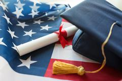 bachelor hat and diploma on american flag - stock photo