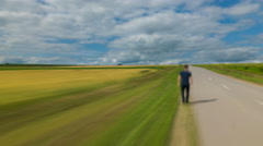 The man walk along the road against the background of cloud stream. Time lapse - stock footage