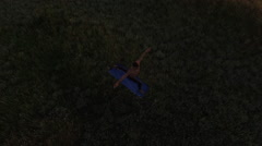 Young sportive man practicing yoga at sunset. Slow motion. Aerial view Stock Footage
