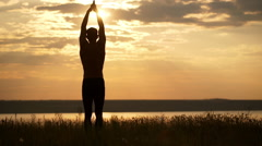 Silhouette of young sportive man practicing yoga at sunset. Slow motion Stock Footage