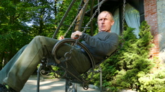 4K . Adult man rides a swing in summer day Stock Footage