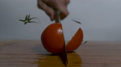 A ripe tomato on a cutting board, a knife cuts it in half in slow motion Stock Footage