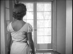 Rear view of woman opening French doors and walking into backyard, 1950s Stock Footage