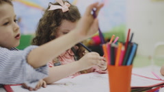 girl drawing with pencils on paper in playroom - stock footage