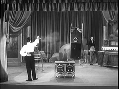 Performer shooting target on stage while female assistant stands by, 1950s Stock Footage