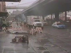 Ambulance following police car under New York City elevated train tracks, 1980s Stock Footage